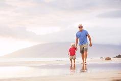 Fader och son som wallking på stranden Royaltyfri Bild