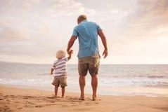 Fader och son som wallking på stranden Royaltyfria Bilder