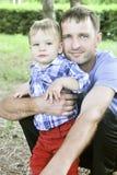 Fader och son tillsammans, med de samma blåa ögonen, blick på kameran Arkivfoton