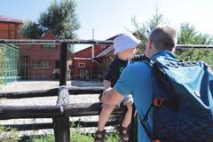 Fader- och sonfamiljtid tillsammans i zoo arkivbild