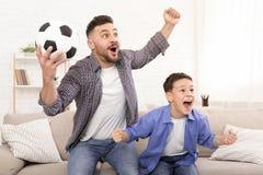 Fader- och sonfotbollfans som hurrar med fotboll, klumpa ihop sig royaltyfria foton