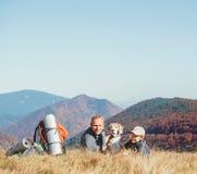 Fader- och sonfotvandrarefotvandrare vilar p? bergkullen med deras beaglehund royaltyfri foto