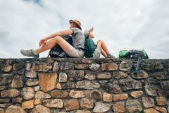 Fader- och sonfotvandrarehandelsresanden vilar tillsammans på gammal stenwa arkivbild