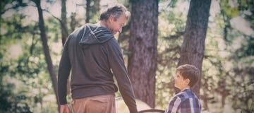 Fader- och soninnehavhänder, medan campa i skog royaltyfri fotografi