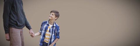 Fader- och soninnehavhänder mot brun bakgrund arkivbild