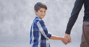 Fader- och soninnehavhänder mot den gråa väggen royaltyfri bild
