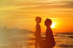 Fader- och soninnehavhänder på solnedgången Royaltyfri Bild