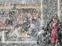 Fader- och sonkorsning honom gata i tungt snöfall och ett ungt par som sitter i en restaurang bak dem arkivbild