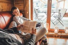 Fader- och sonläsebok som ligger tillsammans på den hemtrevliga soffan i varmt landshus Läsning till den begreppsmässiga bilden f royaltyfria bilder