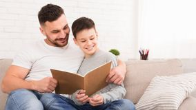 Fader- och sonläsebok som tillsammans spenderar tid hemma royaltyfria bilder