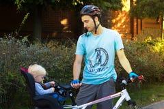 Fader- och sonresanden på cykeln, barn sitter i en cykel Arkivfoto
