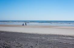 Fader- och sonridningen cyklar längs shorelinen på en strand i Florida Arkivbild