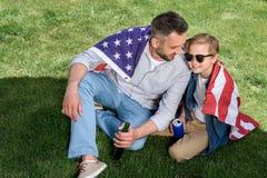 Fader- och sonsammanträde på gräs med oss flagga och hållande öl och sodavatten Royaltyfri Foto