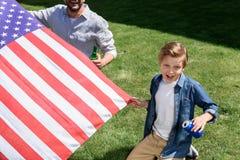 Fader- och sonsammanträde på gräs med oss flagga- och innehavdrinkar Arkivfoton