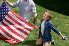 Fader- och sonsammanträde på gräs med oss flagga, skrikig och hållande sodavattencan för pojke Royaltyfri Foto