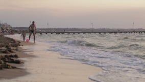 Fader- och sonspring längs stranden med bollen arkivfilmer