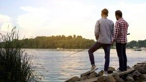 Fader- och tonåringson som tillsammans fiskar och att koppla av nära sjön, favorit- hobby royaltyfri fotografi