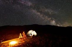 Fader och två sonfotvandrare som har en vila på att campa i berg under natthimmel mycket av stjärnor och den mjölkaktiga vägen royaltyfri foto