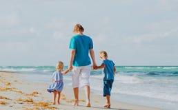 Fader och två ungar som går på stranden Arkivbild