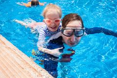 Fader och ungar på simbassängen arkivfoton