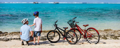 Fader och ungar på stranden med cyklar Fotografering för Bildbyråer