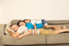 Fader och ungar som sover på soffan Royaltyfri Fotografi