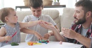 Fader och ungar som spelar med plasticine arkivfilmer