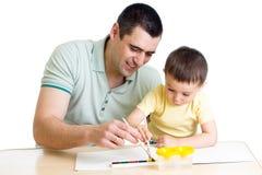 Fader och unge som spelar med målarfärgfärger royaltyfria foton
