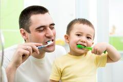 Fader- och ungeson som borstar tänder Fotografering för Bildbyråer