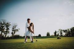 Fader Playing Golf med den lilla dottern på fält royaltyfri fotografi