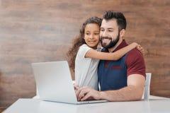 Fader som använder bärbara datorn medan dotter som kramar honom Arkivbilder