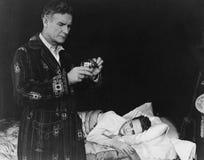 Fader som förbereder medicin för sjuk son (alla visade personer inte är längre uppehälle, och inget gods finns Leverantörgarantie royaltyfria foton