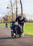 Fader som går med den rörelsehindrade sonen i rullstol Royaltyfri Fotografi