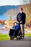Fader som går med den rörelsehindrade sonen i rullstol Royaltyfria Foton