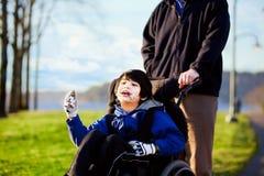 Fader som går med den rörelsehindrade sonen i rullstol Arkivbilder