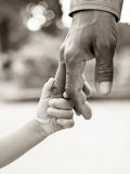 Fader som ger handen till barnet Arkivfoto