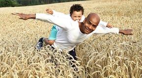 Fader som ger hans son ridtur på axlarna i ett vetefält arkivfoton