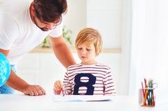 Fader som hjälper hans son med hemmastadd läxa Arkivfoton