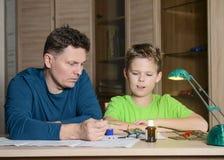 Fader som hjälper hans son med modellnivån Mannen och pojken gör flygplan att modellera Royaltyfria Bilder