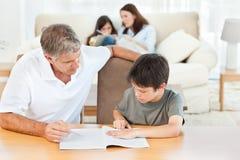 Fader som hjälper henne son med hans läxa 库存照片