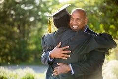 Fader som kramar hans son på hans avläggande av examen royaltyfri bild