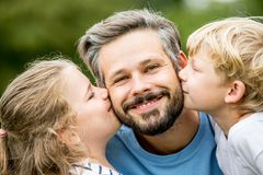 Fader som kyssas av barn royaltyfri foto