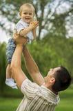 Fader som lyfter sonen i luft Royaltyfri Bild