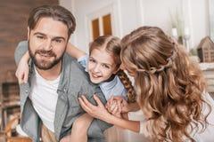 Fader som piggybacking den lyckliga dottern kör den skratta blandade racen för den härliga kameraflickan in mot whi Arkivbilder