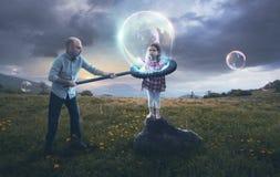 Fader som sätter barnet i en bubbla arkivfoton