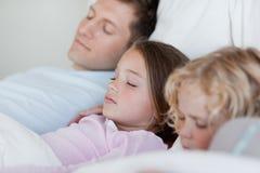 Fader som tar en ta sig en tupplur med hans barn Royaltyfri Bild