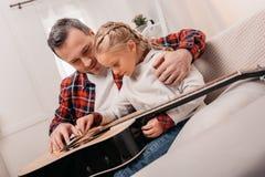 fader som undervisar den förtjusande lilla dottern som spelar den akustiska gitarren arkivbild
