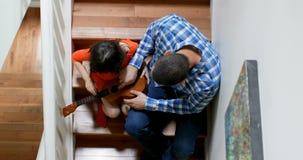 Fader som undervisar hans dotter att spela gitarren på trappuppgången 4k arkivfilmer