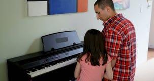 Fader som undervisar hans dotter att spela pianot 4k arkivfilmer