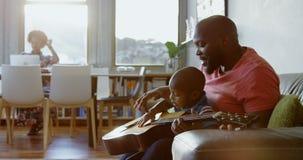 Fader som undervisar hans son hur man spelar gitarren hemmastadd 4k lager videofilmer